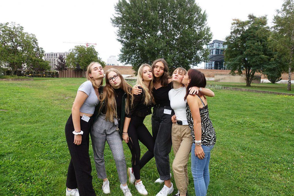 Fünf Mädchen posieren für ein gemeinsames Gruppenfoto im Park.