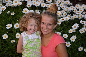 au-pair-australien-mit-kind-auf-blumenwiese-gluecklich
