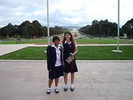 schueleraustausch-australien-maedchen-schuelgebaeude-uniform-wiese